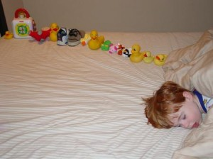 Boy sleeping with toys lined up in a row